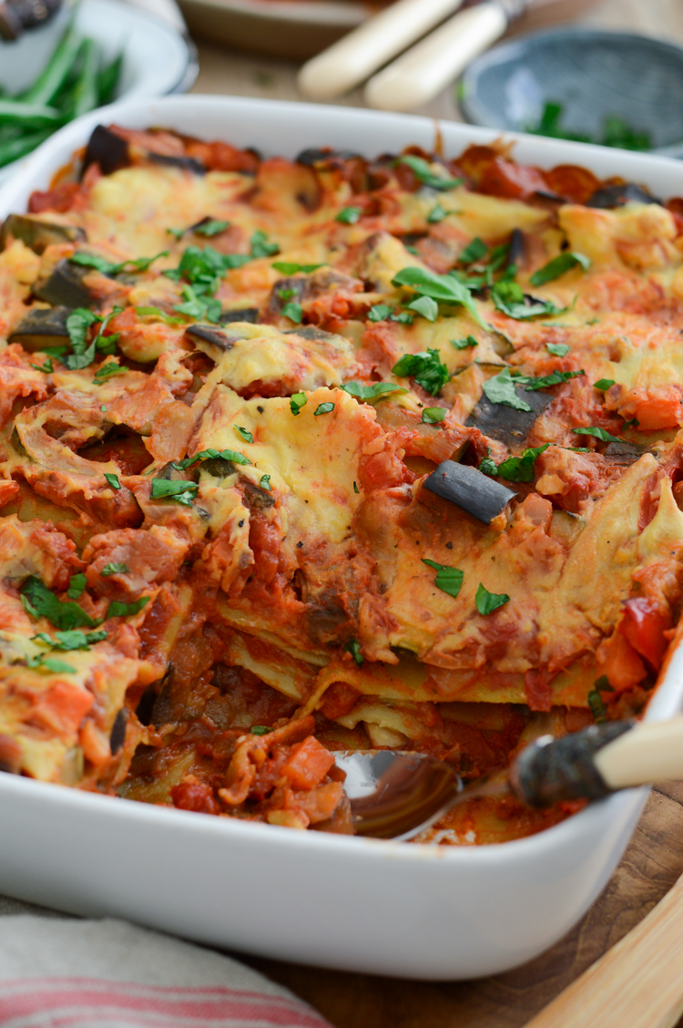 Close up of vegan lasagna in a white dish on the wooden table, served with green vegetables