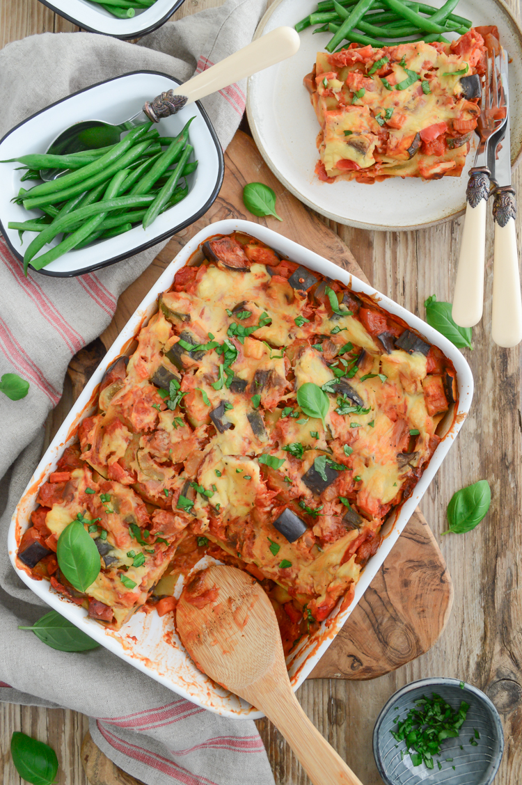 Top down view of vegan lasagna in a white dish on the wooden table, served with green vegetables