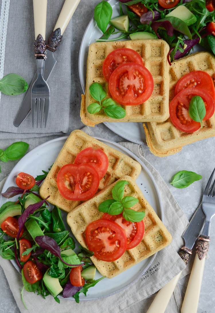 two plates of vegan chickpea waffles with a side salad and sliced tomatoes