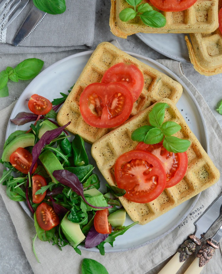 a plate with vegan chickpea waffles with a side salad and sliced tomatoes