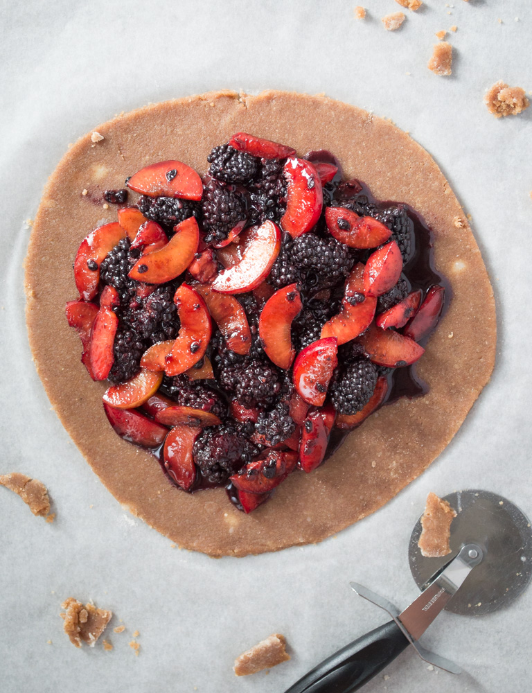 Top down view of stewed plums and blackberries on galette dough