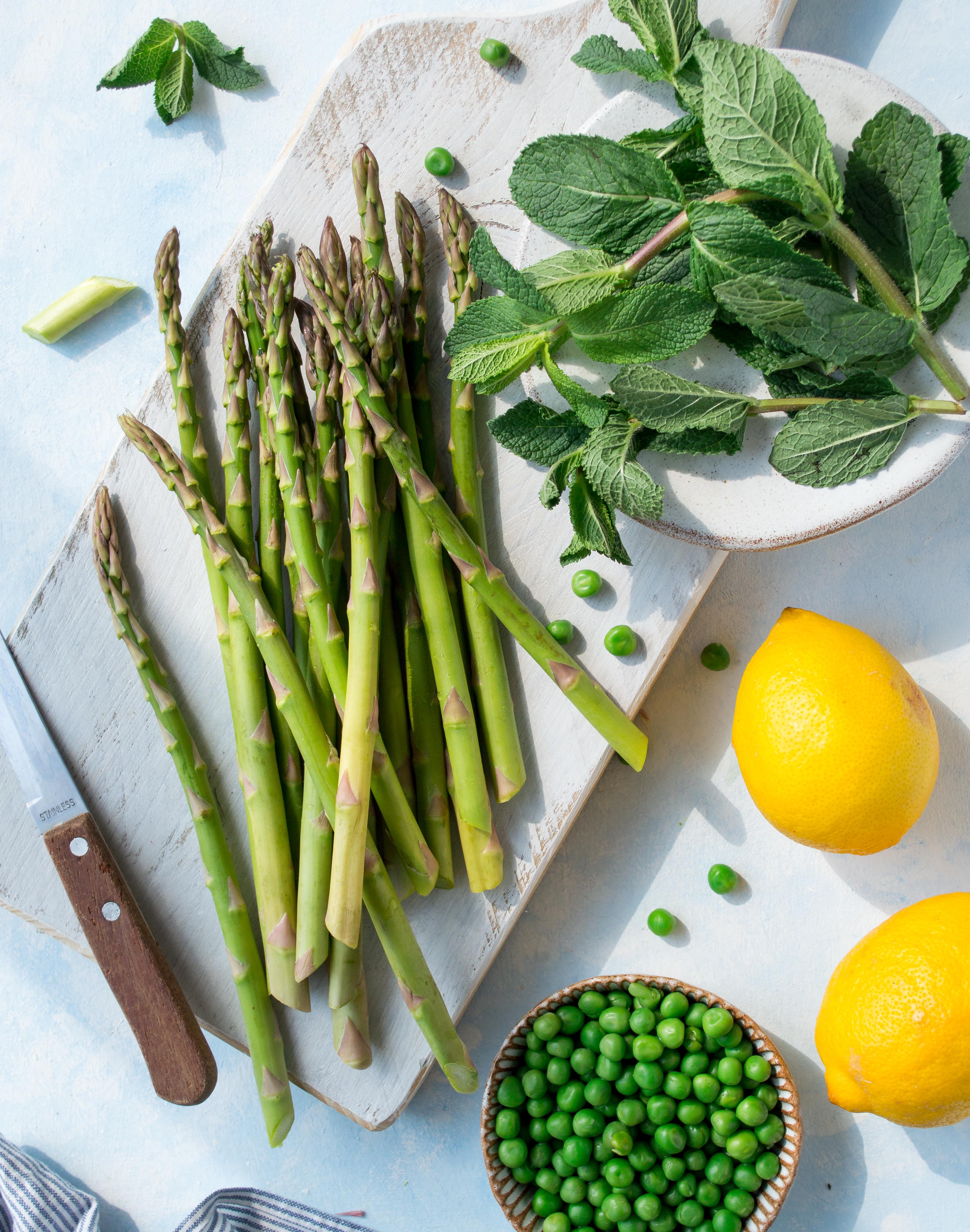 Overhead shot of asparagus, mint, peas, lemons