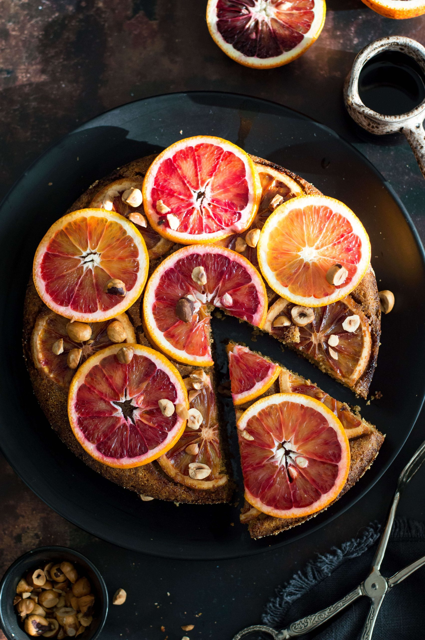 Top down view of upside down blood orange cake on a black plate