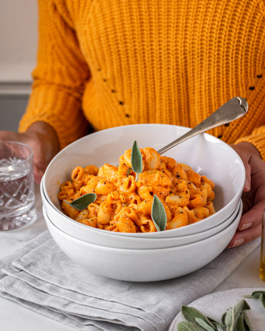 A white bowl of vegan mac and cheese on the table, hands holding the bowl