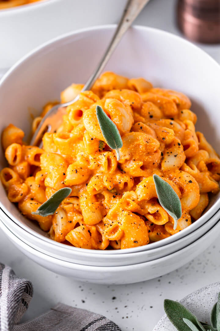 Vegan mac and cheese in a white bowl garnished with sage leaves