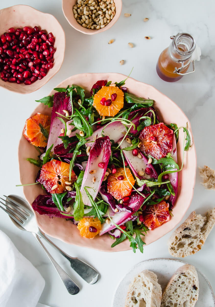 Top down view of chicory salad with rocket & blood oranges in a pink bowl