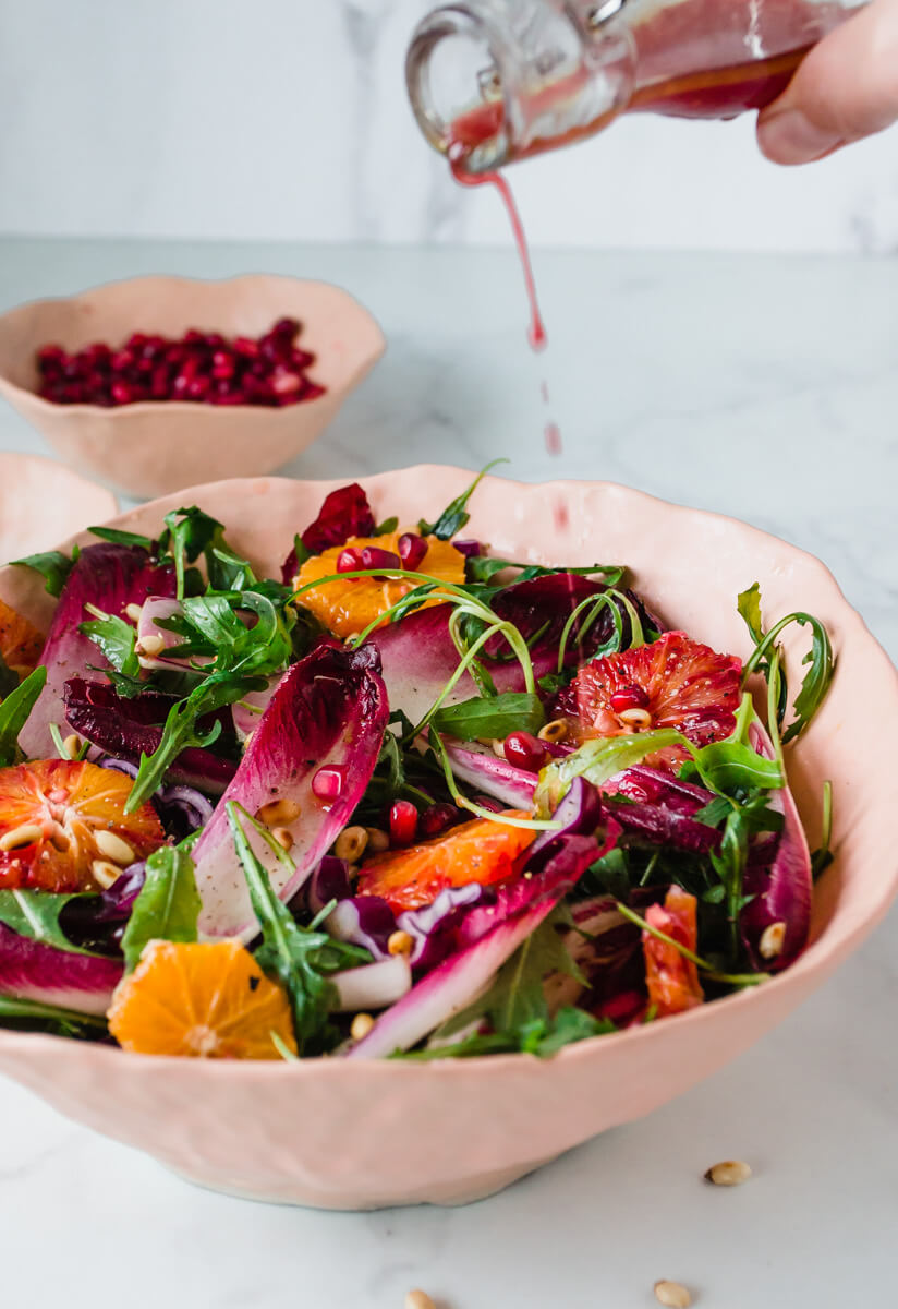 Close up view of chicory salad with rocket & blood oranges with pouring the dressing