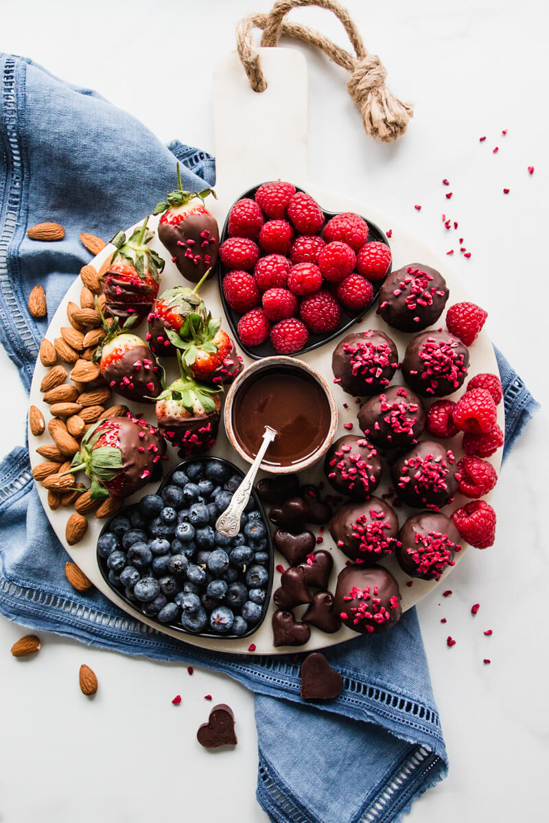 Round white platter with fruit, berries and chocolate date balls