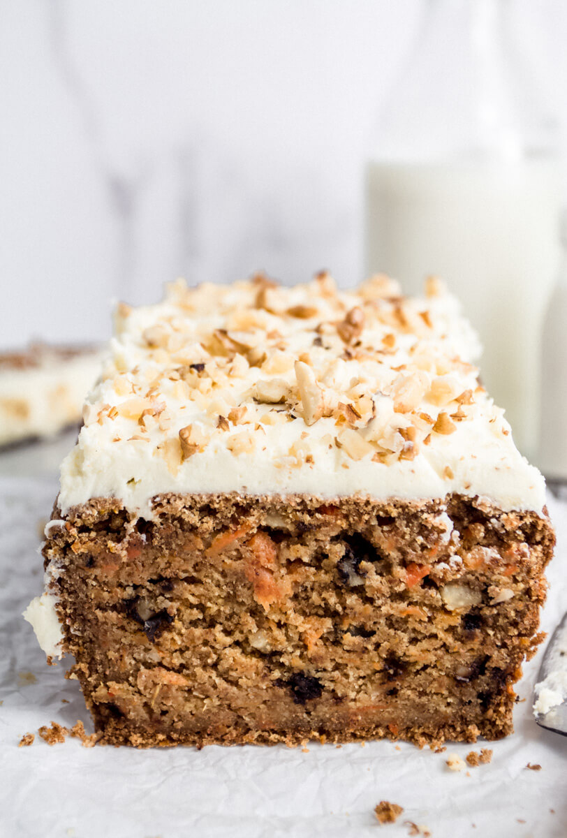 Close up view of vegan carrot cake covered with buttercream frosting & walnuts