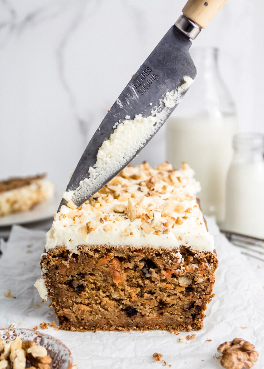 Close up view of cutting a vegan carrot cake with a knife