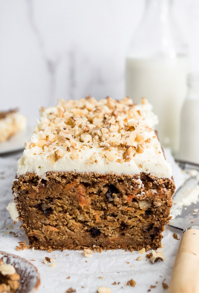 Close up view of a sliced vegan carrot cake loaf with buttercream icing