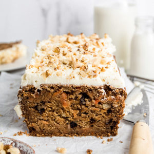 Close up view of a sliced vegan carrot cake loaf, knife on the side