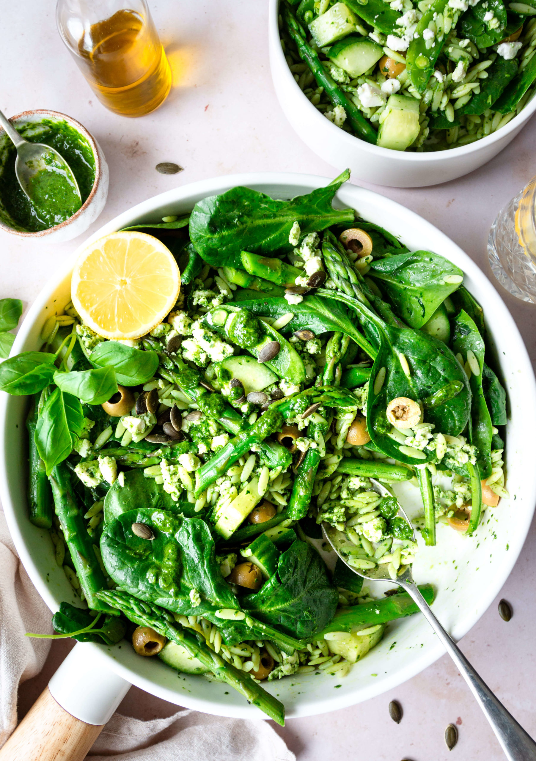 Top down view of green orzo salad in a white bowl