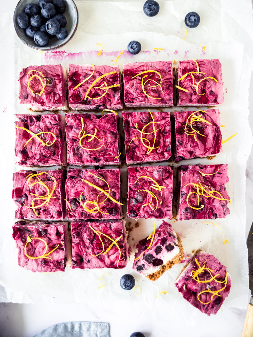 Overhead view of vegan blueberry lemon cheesecake bars on a white board