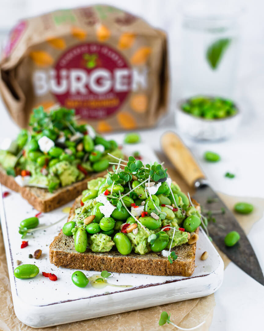 Vegan avocado toast with edamame beans & feta on a white board , bread loaf in the background
