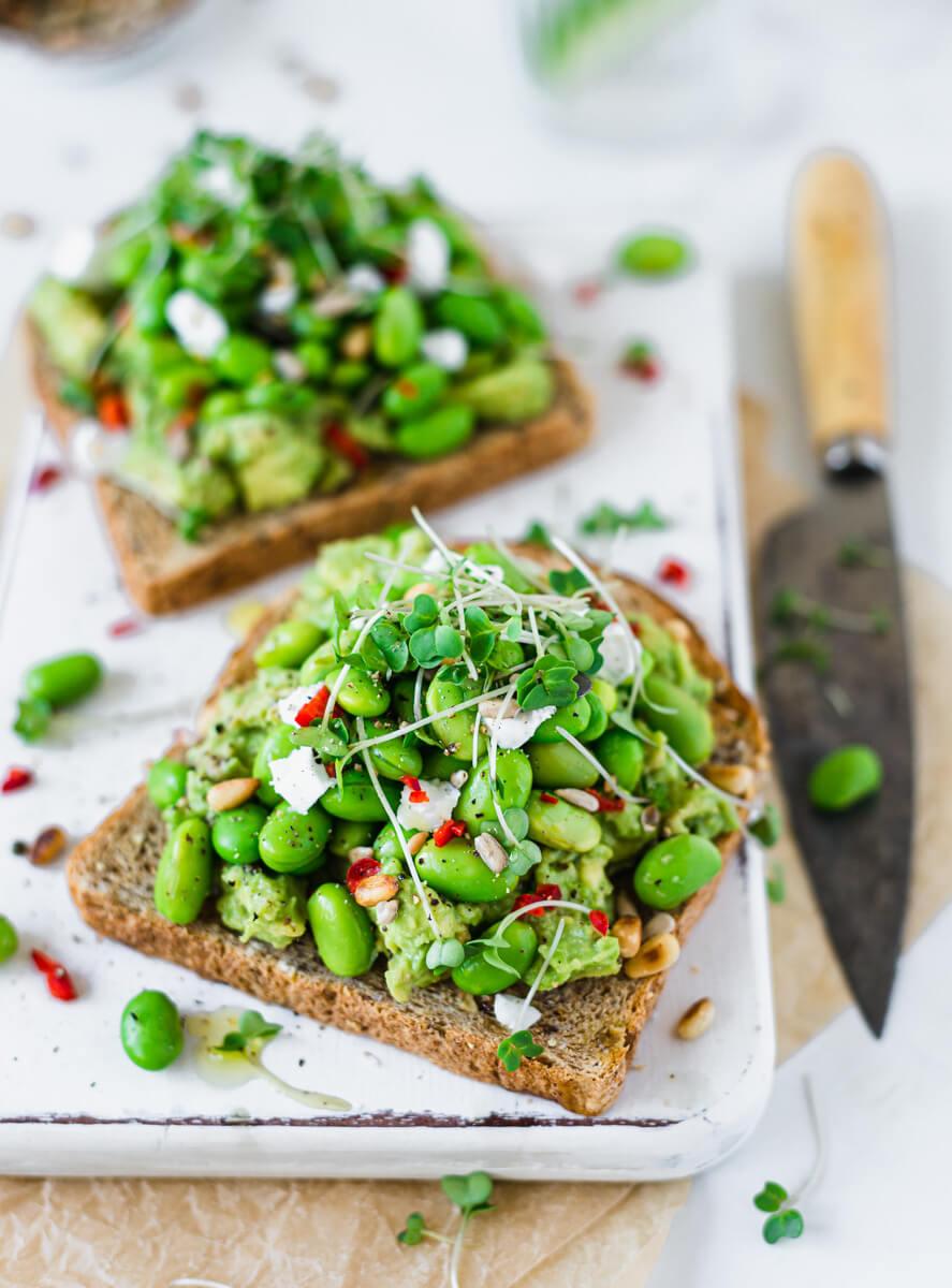 Vegan avocado toast with edamame beans & feta on a white board