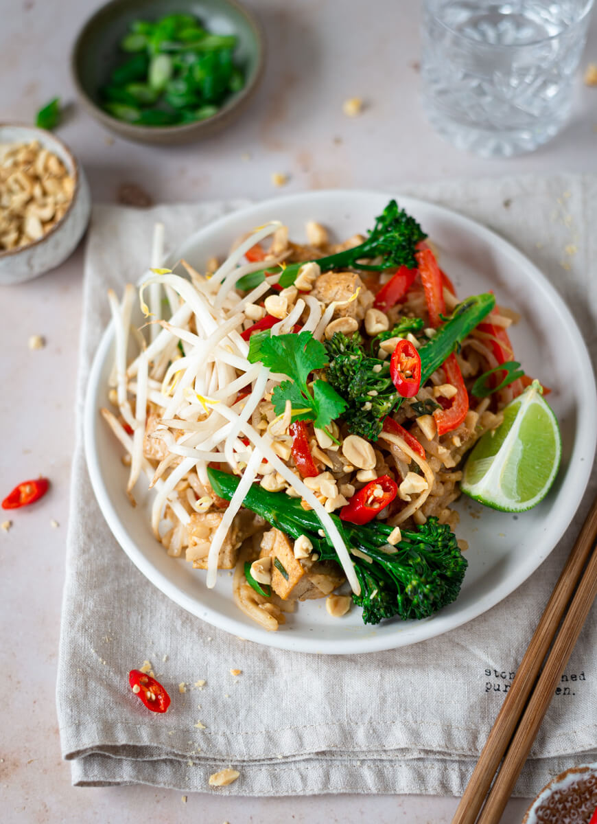Vegan Pad Thai on a plate with lime wedges & broccoli
