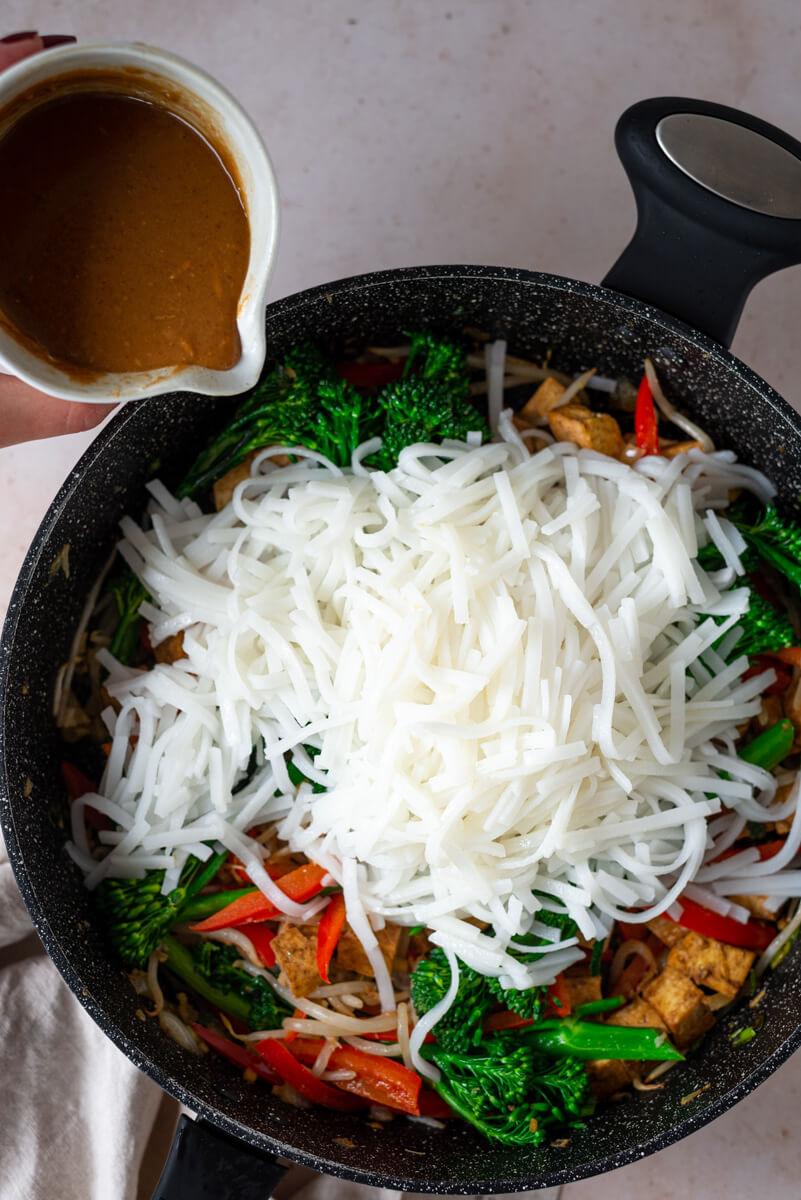 Overhead view of vegan Pad Thai in a black pan