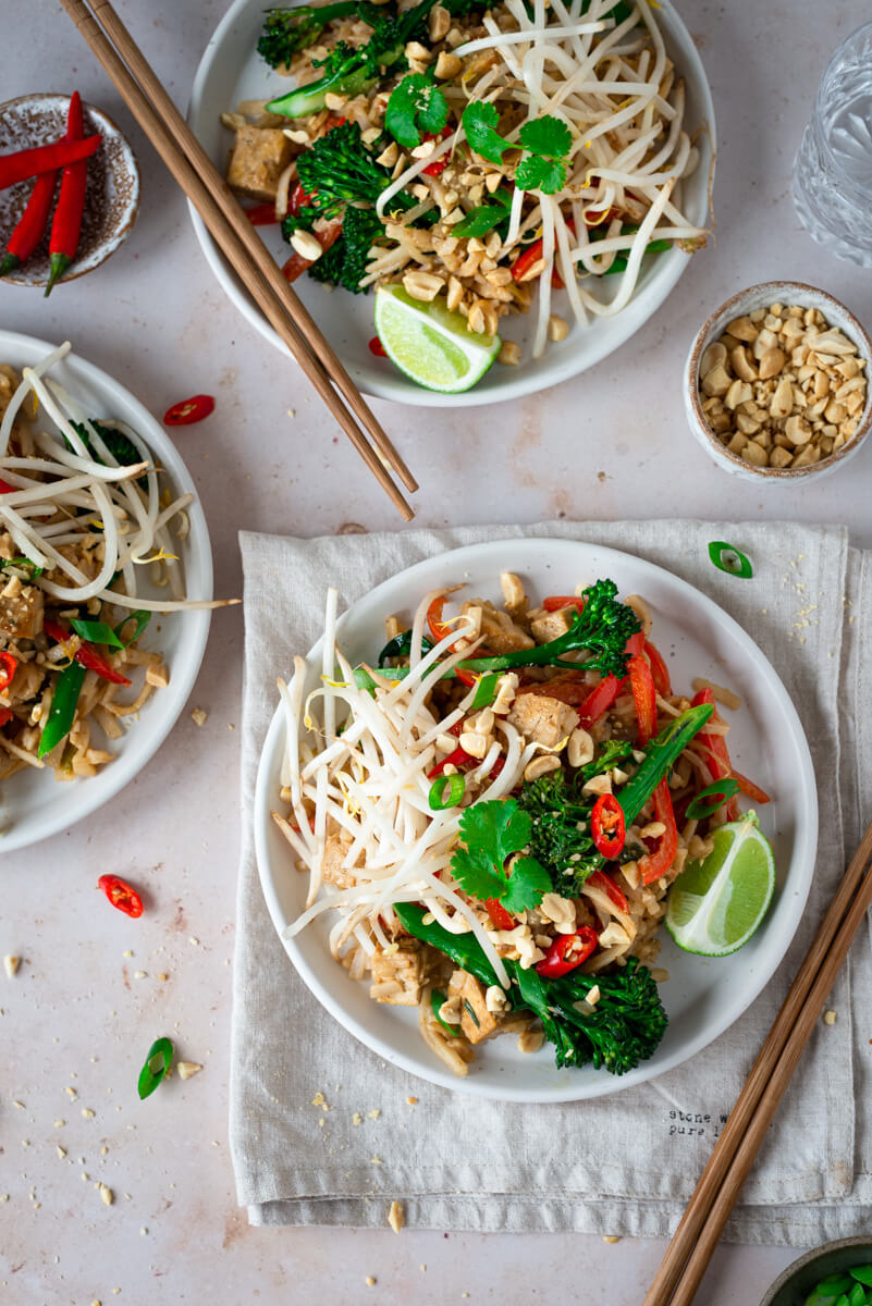 Overhead view of vegan Pad Thai on white plates with lime wedges & broccoli